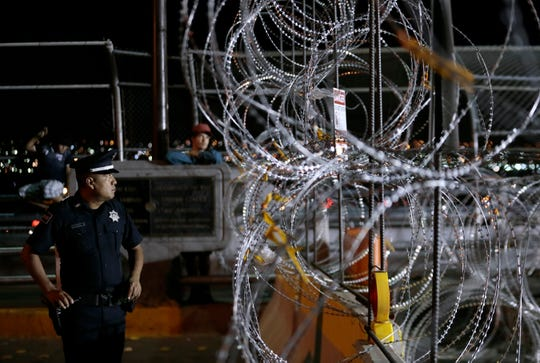 A Mexican federal police officer stares through concertina wire after U.S. Customs and Border Protection closed the Paso Del Norte Bridge between El Paso, Texas, and Juárez, Mexico, on Friday, Aug. 16, 2019.