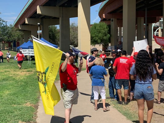 Open Carry Texas El Paso Chapter members Chris Yost, left, and James Peinado, both holding flags, protested the El Paso Strong anti-gun rally on Saturday, Aug. 17, 2019, at Lincoln Park.