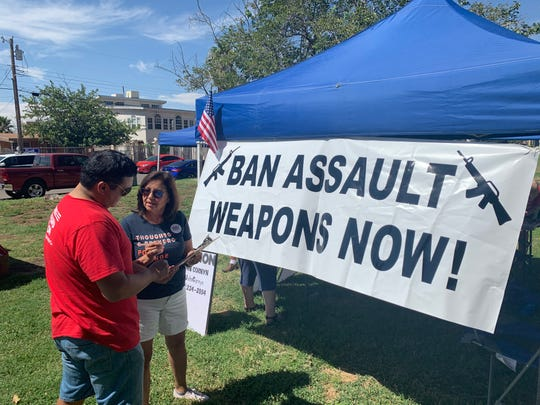 Onward Together Grassroots El Paso member Javier Aaron Paz and Yvonne Hernandez-Daniels were handing out postcards Saturday, Aug. 17, 2019, in Lincoln Park addressed to U.S. Senate Majority Leader Mitch McConnell, R-Kentucky, calling for a ban on assault rifles.