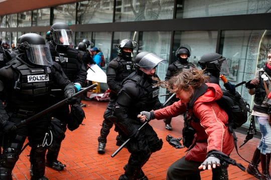 In the Feb. 20, 2017, file photo, protesters clash with police in Portland, Ore. Portland is again expected to be a flashpoint because of a right-wing rally planned Saturday, Aug. 17, 2019, in the liberal city. The out-of-town groups will likely be met by anti-fascist protesters and the police will be out in force. The city has seen violent protests before.