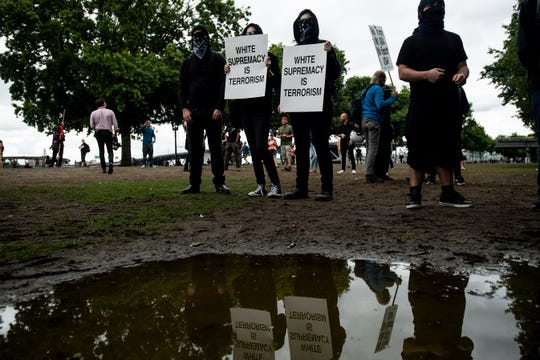 "Black-clad protesters, gathered to oppose conservative groups staging an ""End Domestic Terrorism"" rally, hold signs in Portland, Ore., on Saturday, Aug. 17, 2019. Police have mobilized to prevent clashes between conservative groups and counter-protesters who plan to converge in the city."