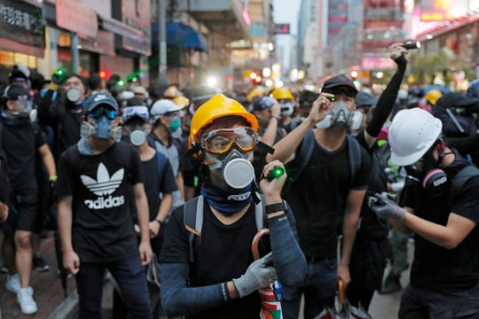 Protesters use laser pointers beam at policemen during the anti-extradition bill protest in Hong Kong Saturday, Aug. 17, 2019. Another weekend of protests is underway in Hong Kong as Mainland Chinese police are holding drills in nearby Shenzhen, prompting speculation they could be sent in to suppress the protests.