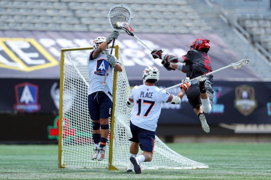 Chaos' Connor Fields (5) leaps to shoot as Archers goalie Adam Ghitelman (8) reaches for the save while Archers' Jackson Place (17) defends during a Premier Lacrosse League game in Hamilton, Ontario, on Aug. 17, 2019.
