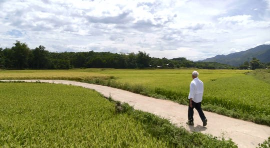 In an image provided by ESPN from video, Rocky Bleier walks in Hiep Duc Valley, about 35 miles south of Danang in Vietnam, on Aug. 20, 2018.