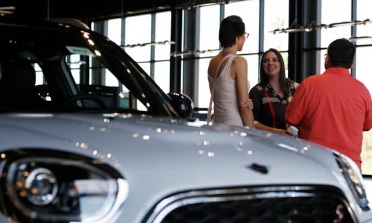 In this Aug. 30, 2018, file photo, a salesperson confers with two customers interested in the 2018 Countryman on display in the showroom of a Mini dealership in Highlands Ranch, Colo. Choosing a smaller vehicle, leasing, or buying a used vehicle are a few of the recommended methods in lowering a car payment.