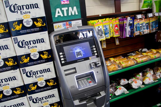 In this April 18, 2018, file photo, an ATM machine is in use at a New York convenience store. If you find yourself short on cash while on vacation, it might seem easiest to hit up the nearest ATM. But if that handy machine is not in your bank's network, you could get a double whammy of fees: The ATM owner will probably charge a few dollars for the convenience, and your own bank may tack on an extra $2.50 or so.