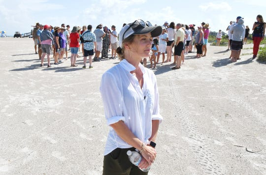 Stephanie Young McCluney, wife of Brian McCluney, one of two missing boaters, is joined by supporters who gathered at Jetty Park Aug. 18 to pray and search the shore for any clues in the search for the missing boaters who left Port Canaveral.