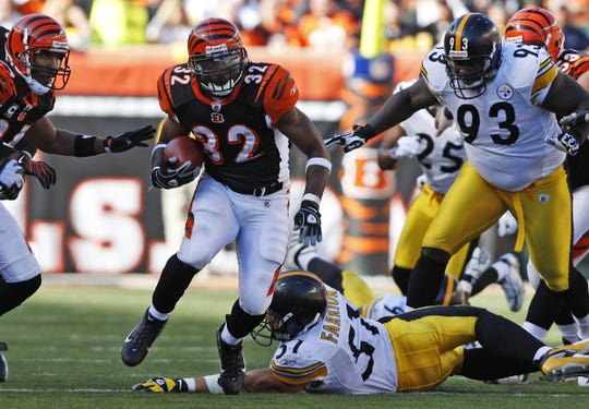 Cincinnati Bengals halfback Cedric Benson runs the ball and finds a hole in the fourth quarter past the Pittsburgh Steelers (51) James Farrior and (93) Nick Eason at Paul Brown Stadium Sunday  October 19, 2008. The Enquirer/Jeff Swinger