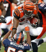 Cincinnati Bengals running back Cedric Benson (32) runs over Denver Broncos Wesley Woodyard (59) in the 1st quarter. Cincinnati Bengals and the Denver Broncos battle in a NFL preseason game at Paul Brown stadium August 15, 2010 in Cincinnati. The Enquirer/ Joseph Fuqua II
