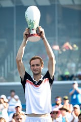 Daniil Medvedev holds the Rookwood Trophy after defeating David Goffin in the Western & Southern Open tennis tournament men's finals match on Sunday, Aug. 18, 2019, in Mason. Medvedev won 7-6, 6-4.
