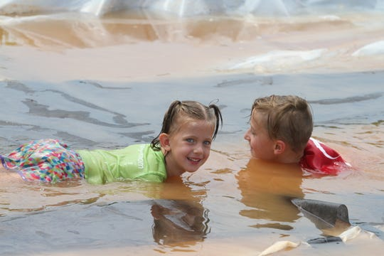 """Children cooled off in the water obstacle during the inaugural """"Carry-Thee"""" wife carrying contest on Saturday, August, 17, 2019."""