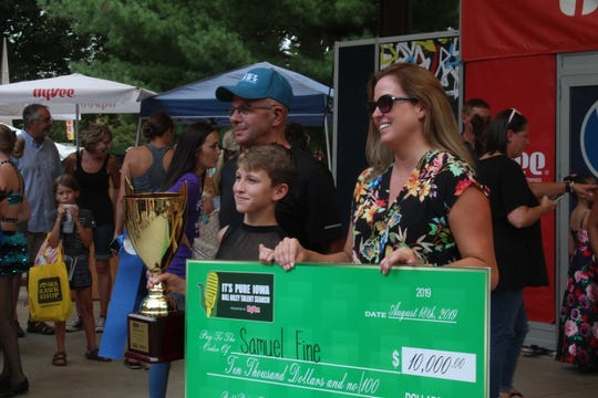 Bill Riley Talent Search senior champ Samuel Fine and his mother, Jessica Fine, hold up his $10,000 award, presented at the Iowa State Fair after the competition ended. Jessica Fine said she needed to keep her sunglasses on to hide that she was tearing up.