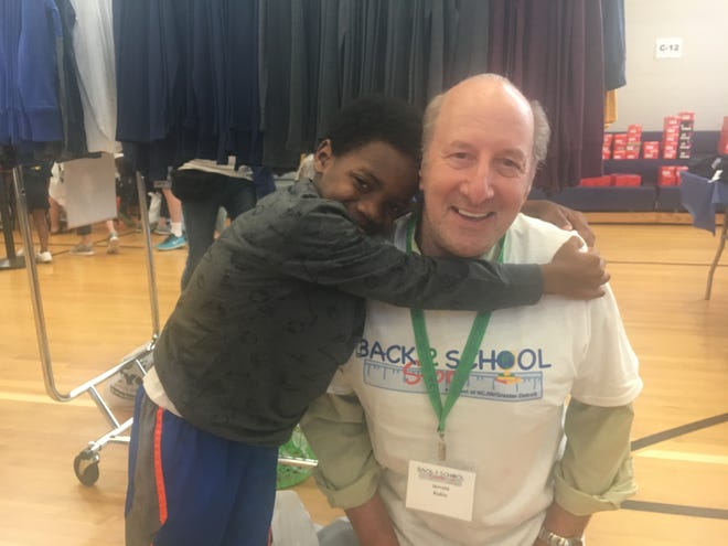 Demarco McCool, 8, hugs volunteer Jerrold Rubin during the Back 2 School Store event at Munger Elementary-Middle School in Detroit on  Sunday, Aug. 18, 2019.