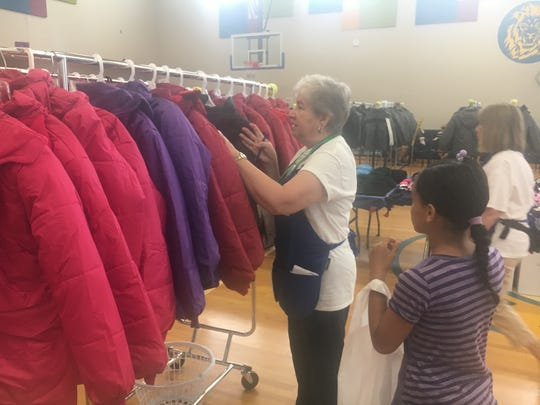 Volunteer Suzanne Simon helps Grace Benitez, 10, find a winter coat to take home at the Back 2 School Store event at Munger Elementary-Middle School in Detroit on Sunday, Aug. 18, 2019.