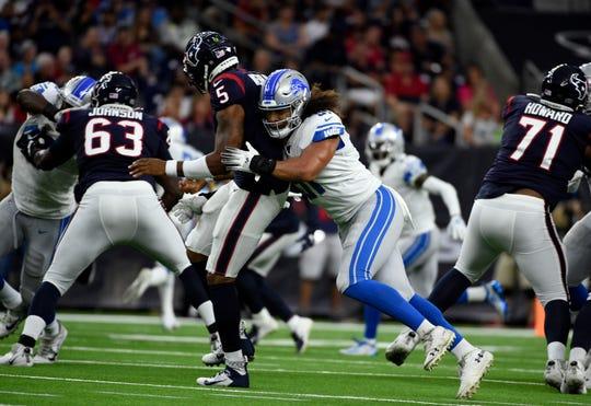 Detroit Lions linebacker Jahlani Tavai hits Houston Texans quarterback Joe Webb III during the first half.