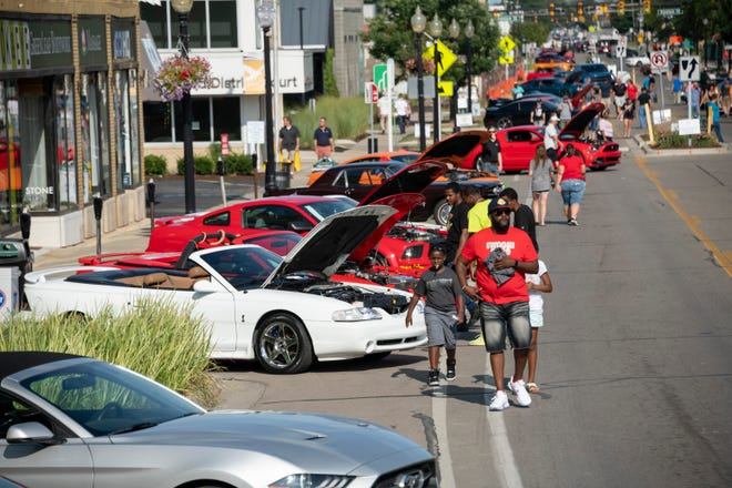 Car enthusiasts walk through Mustang Alley on Nine Mile in Ferndale during the Woodward Dream Cruise.