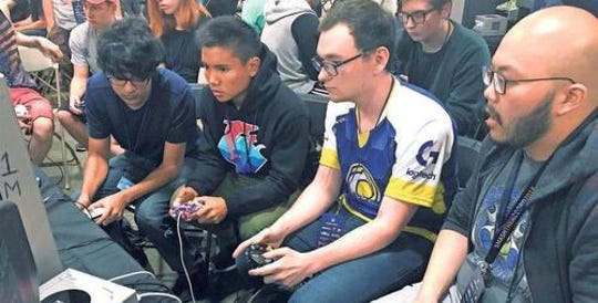 "Connor Nguyen, at right, and Griffin Williams, second from right, compete in a ""Super Smash Bros. Melee"" tournament Aug. 25, 2017, at the Shine eSports festival at the Seaport World Trade Center in Boston. Williams is captain of an esports team at the University of California, Irvine."
