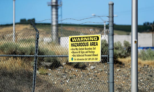 In this Wednesday, Aug. 14, 2019 photo, a sign at the Hanford Nuclear Reservation warns of possible hazards in the soil there along the Columbia River near Richland, Wash. Washington state officials are worried that the Trump administration wants to reclassify millions of gallons of wastewater at Hanford from high-level radioactive to low-level, which could reduce cleanup standards and cut costs. (AP Photo/Elaine Thompson)