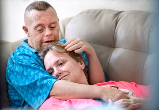 Jimmy Wilson holds his wife, Kelly, as the two sit on the couch watching television, on July 31, 2019, at their home in Janesville, Wis. Jimmy, who has Down Syndrome, married Kelly 25 years ago.