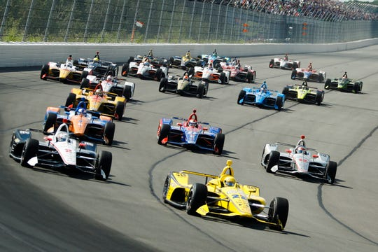 Drivers led by Simon Pagenaud (22) enter Turn 1 after taking the green flag to start the IndyCar Series auto race at Pocono Raceway, Sunday, Aug. 18, 2019, in Long Pond, Pa.