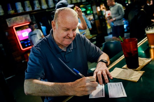 Dennis Foreback writes the names of the songs he'd like to perform while waiting for karaoke to start at Crunchy's on Thursday, Aug. 15, 2019, in East Lansing.