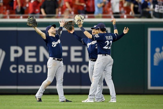 Milwaukee Brewers' Ryan Braun, left, Trent Grisham, center, and Christian Yelich celebrate after the team's win over the Washington Nationals on Aug. 18.