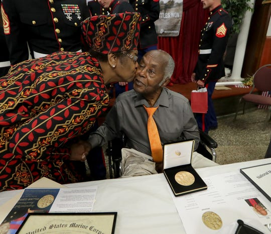 Milwaukee Marine veteran William Coffer Jr. gets a kiss on the cheek from longtime friend and Greater Galilee Missionary Baptist Church member Vicki Butler after receiving the Congressional Gold Medal.