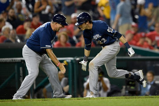 ' Christian Yelich, celebrates his home run with third base coach Ed Sedar in the 13th inning to give the Brewers a 13-12 lead Saturday night.