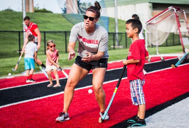 Field hockey head coach Stephanie Bernthal teaches an attendee dribbling skills during Fan Jam at Scheumann Stadium Saturday, Aug. 17, 2019.