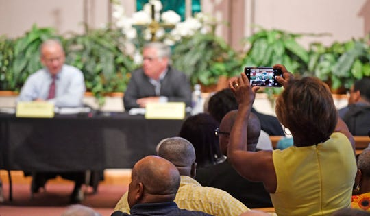 A guest takes a photo of Mayor David Briley and At-large Council Member John Cooper as they speak at the NOAH mayoral forum at Fifteenth Ave Baptist Church   Sunday, Aug. 18, 2019, in Nashville, Tenn.