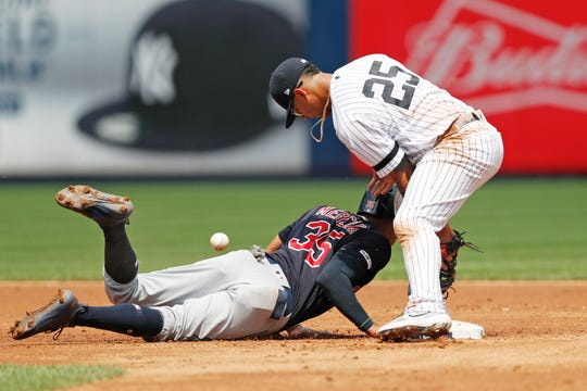 New York Yankees' second baseman Gleyber Torres (25) drops the ball as Cleveland Indians' Oscar Mercado (35) slides back to second on a pickoff-attempt during the first inning of a baseball game, Sunday, Aug. 18, 2019, in New York. (AP Photo/Kathy Willens)