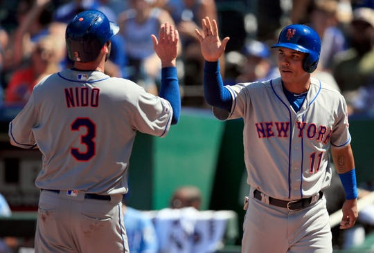 New York Mets' Tomas Nido (3) and Ruben Tejada (11) celebrate after scoring in the seventh inning of a baseball game against the Kansas City Royals at Kauffman Stadium in Kansas City, Mo., Sunday, Aug. 18, 2019. (AP Photo/Orlin Wagner)
