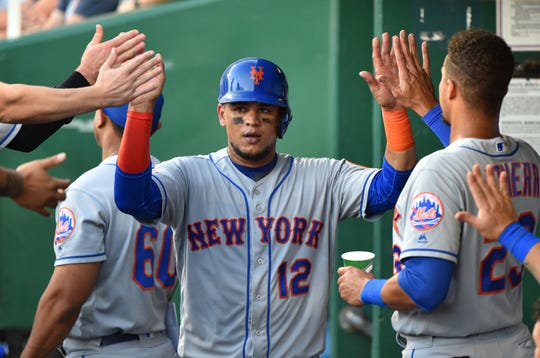Juan Lagares #12 of the New York Mets celebrates with teammates after scoring on a Joe Panik single in the fifth inning against the Kansas City Royals at Kauffman Stadium on August 17, 2019 in Kansas City, Missouri.