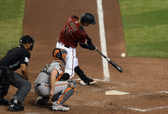 Aug 18, 2019; Phoenix, AZ, USA; Arizona Diamondbacks second baseman Wilmer Flores (41) hits a solo home run against the San Francisco Giants during the fifth inning at Chase Field. Mandatory Credit: Joe Camporeale-USA TODAY Sports