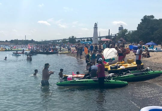 Hundreds of visitors and residents cross Lighthouse Beach to get into the southern end of Lake Huron and float down the St. Clair River as part of the 2019 Port Huron Float Down on Sunday, Aug. 18.