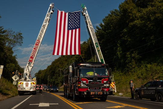 Buchanan Valley Rescue-Engine 27 carries the casket of Buchanan Valley Fire Department Assistant Chief Walter Wagaman through a flag arch to bring him home to Buchanan Valley for the first time since his death during a procession after his funeral services, Sunday, Aug. 18 in Orrtanna. Assistant Chief Wagaman died on Aug. 14 after sustaining severe injuries in the line of duty on Aug. 2 when he fell from a fire engine responding to a vehicle crash.