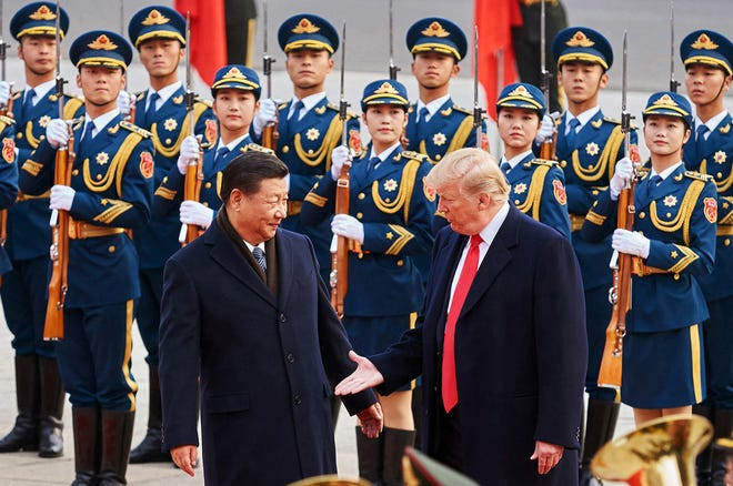 From left, China's President Xi Jinping and U.S. President Donald Trump shake hands on Nov. 9, 2017, during a meeting outside the Great Hall of the People in Beijing. Trump has delayed many new tariffs on Chinese imports until December. (Artyom Ivanov/Tass/Abaca Press/TNS)