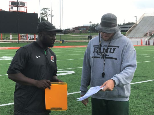 FAMU student assistant coach Myron Dillard (left) goes over the play script for a scrimmage with graduate assistant coach Mateo Kambui.