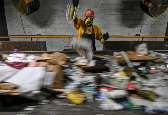 Ylget Metelus, a temporary worker from Manpower at the St. Lucie County Solid Waste Bailing & Recycling Facility, pre-sorts through incoming recyclables as they quickly pass by on a conveyor belt, Wednesday, July 31, 2019, in Fort Pierce. Pre-sorters are looking for dangerous materials coming from collected recycle bins as the content enters the single-stream recycling system.