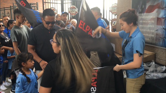 El Paso Locomotive fans collect an El Paso Strong flag before the game against the Tacoma Sounders2 at Southwest University Park Saturday night