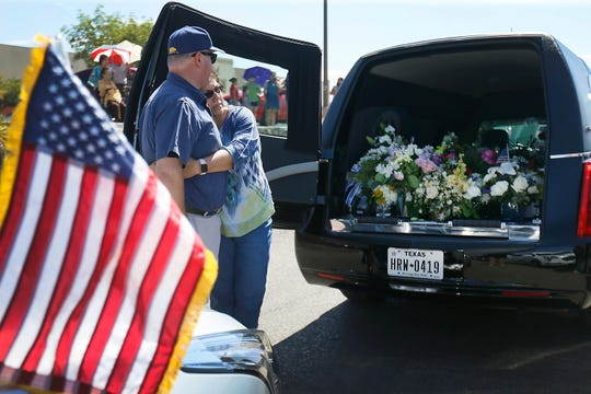 Elizabeth Flores hugs her husband, David Casillas, while watching representatives from funeral homes place flowers at the Walmart shooting memorial site Sunday, Aug. 18, 2019, in El Paso, Texas. A procession of 22 hearses filled the memorial site to honor all of the victims of the Aug. 3, 2019, attack. The flowers were sent from across the world for the funeral services for Margie Reckard.