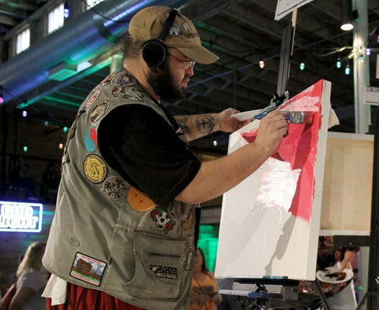 Cliff Womble paints during Art Battle Saturday, Aug. 17, 2019, in The Warehouse.