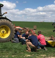 "Ryan Elbe, right, shows the Brewers' grounds crew the equipment they use on Golden ""E"" Dairy in Washington County."