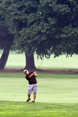 Brad Baker hits an iron shot through the rain on the 17th hole during the final round of the Zanesville District Golf Associaiton Senior Amateur on Saturday at Zanesville Country Club. Baker, from Warsaw, shot 72 to earn his third straight title.