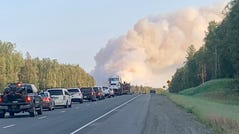 Smoke billows in the distance as traffic backed up near Mile 95 of the George Parks Highway near the Montana Creek Campground early Saturday evening. The McKinley Fire had burned as many as 140 acres by 5 p.m. and stopped service on the Alaska Railway in both directions after fire reportedly jumped the tracks.