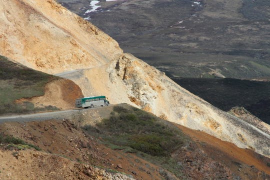 This May 27, 2016, photo shows a tourist bus near Polychome Pass on the only road inside Denali National Park and Preserve, Alaska. Park officials on Friday, Aug. 16, 2019, closed the park road at Mile 30 of the 92-mile road after a culvert washout and several mudslides in the area surrounding Polychome Pass and Eielson Visitor Center created unsafe conditions. Park officials say 300 tourists were inside the park, on the other side of the road closure.