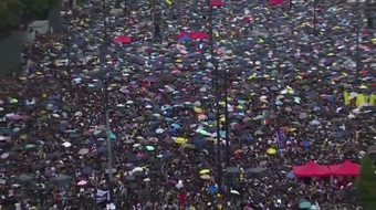 Hong Kong democracy activists gather to protest amidst the rain on Sunday,