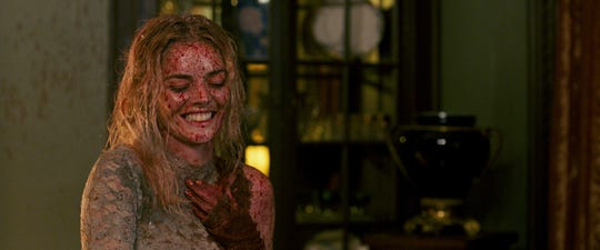 "Grace (Samara Weaving) gets covered in blood and guts but still manages a grin in ""Ready or Not."""