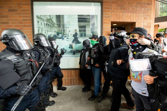 "Police officers face off against protesters opposed to right-wing demonstrators following an ""End Domestic Terrorism"" rally in Portland, Ore., on Aug. 17, 2019."