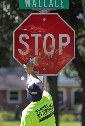 Karel Wardlow, Midwest Restoration, works to remove graffiti from the a stop sign on Thursday, August 15, 2019, in Combined Locks, Wis. Midwest Restoration is providing free graffiti removal to communities in the Fox Valley.